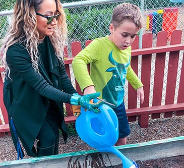 Teacher showing special needs child how to water a garden