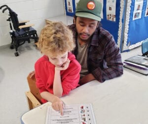 Autism school classroom with teacher helping special needs student