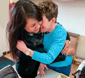 Special needs adult hugging teacher at Bay Area School